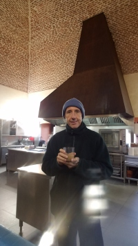 Stealing a warm cup of café con leche in the kitchen